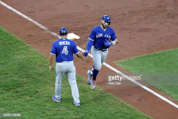 Kevin Pillar of the Toronto Blue Jays celebrates his second inning solo home run with third base coach Luis Rivera against the Baltimore Orioles at...