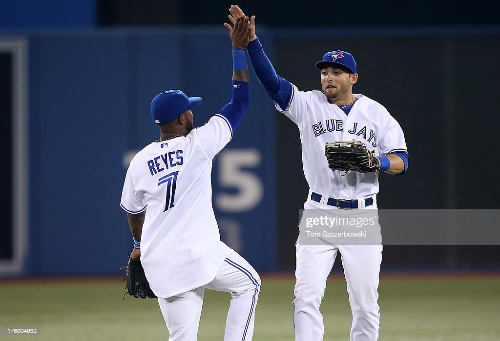 Kevin Pillar #22 of the Toronto Blue Jays celebrates their victory with Jose Reyes #7 during MLB game action against the New York Yankees on August 26, 2013 at Rogers Centre in Toronto, Ontario, Canada.