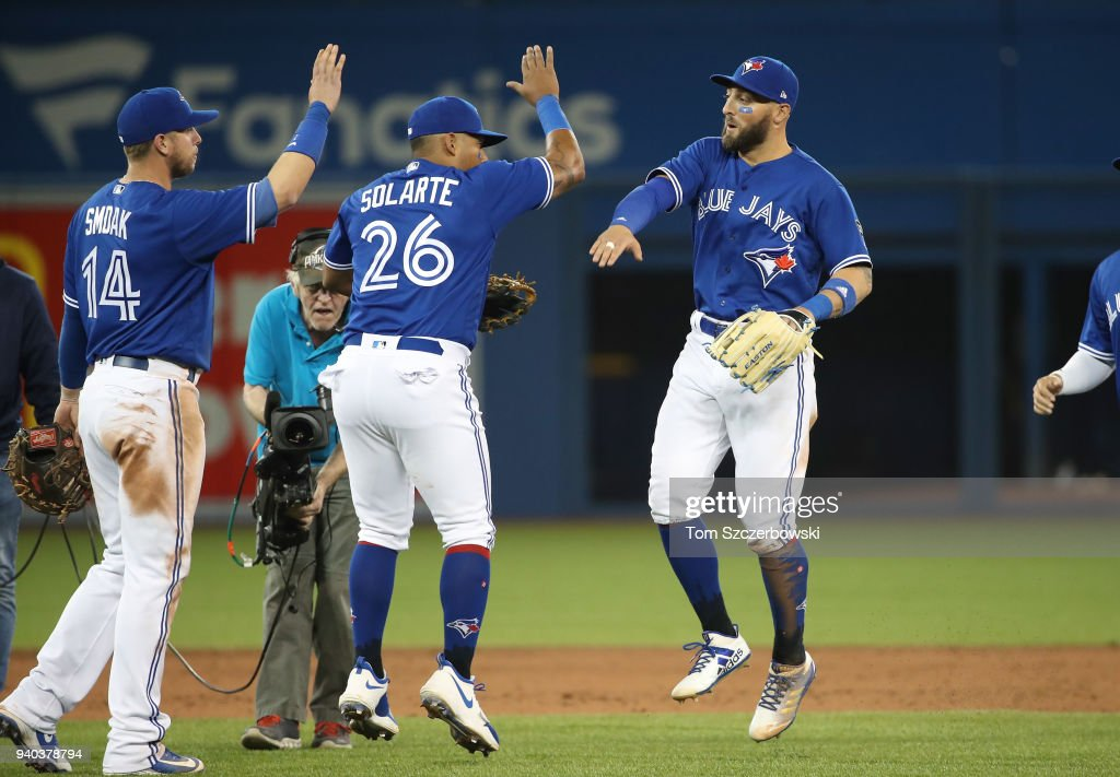 Kevin Pillar #11 of the Toronto Blue Jays celebrates their victory with Yangervis Solarte #26 during MLB game action against the New York Yankees at Rogers Centre on March 31, 2018 in Toronto, Canada.