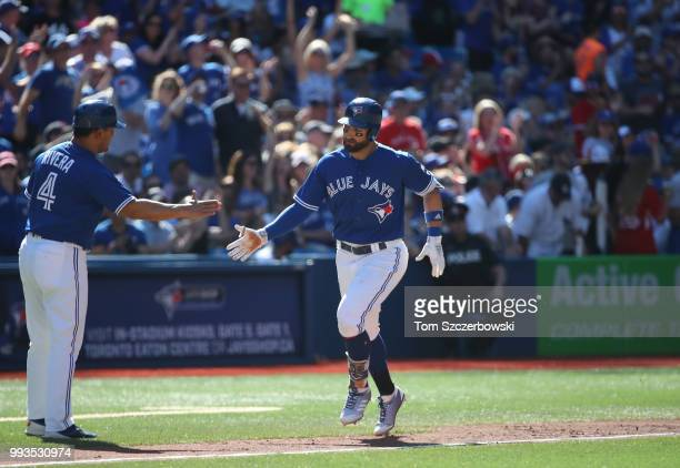 Kevin Pillar of the Toronto Blue Jays circles the bases and is congratulated by third base coach Luis Rivera after hitting a tworun home run in the...