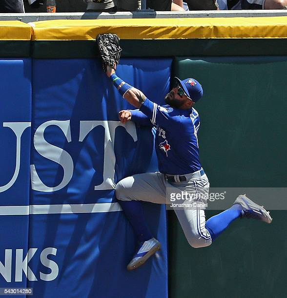 Kevin Pillar of the Toronto Blue Jays collides with the wall trying to catch a home run ball that gets stuck in the padding hit by Brett Lawrie of...