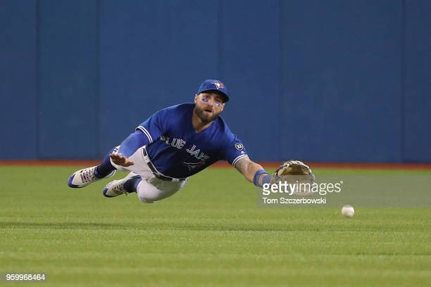 Kevin Pillar of the Toronto Blue Jays dives but cannot catch a bloop double hit by Jed Lowrie of the Oakland Athletics in the sixth inning during MLB...