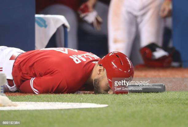 Kevin Pillar of the Toronto Blue Jays falls to the turf after being hit by a foul ball while standing in the ondeck circle in the ninth inning during...