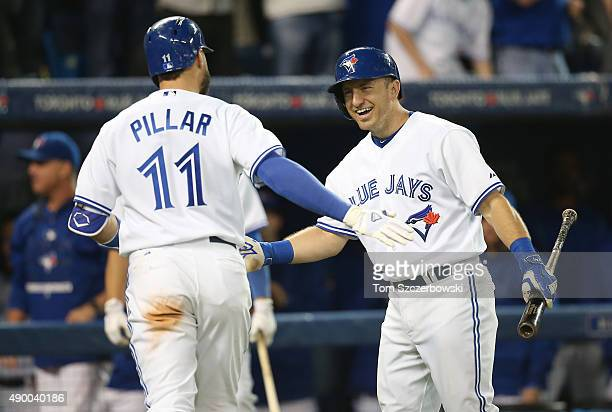 Kevin Pillar of the Toronto Blue Jays is congratulated by Cliff Pennington after hitting a solo home run in the fourth inning during MLB game action...