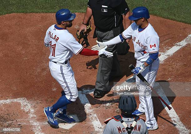 Kevin Pillar of the Toronto Blue Jays is congratulated by Ryan Goins after hitting a tworun home run in the second inning during MLB game action...
