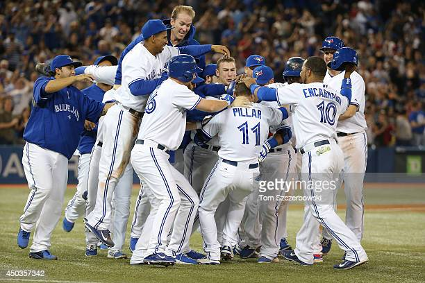 Kevin Pillar of the Toronto Blue Jays is congratulated by teammates after his gamewinning single in the ninth inning during MLB game action against...