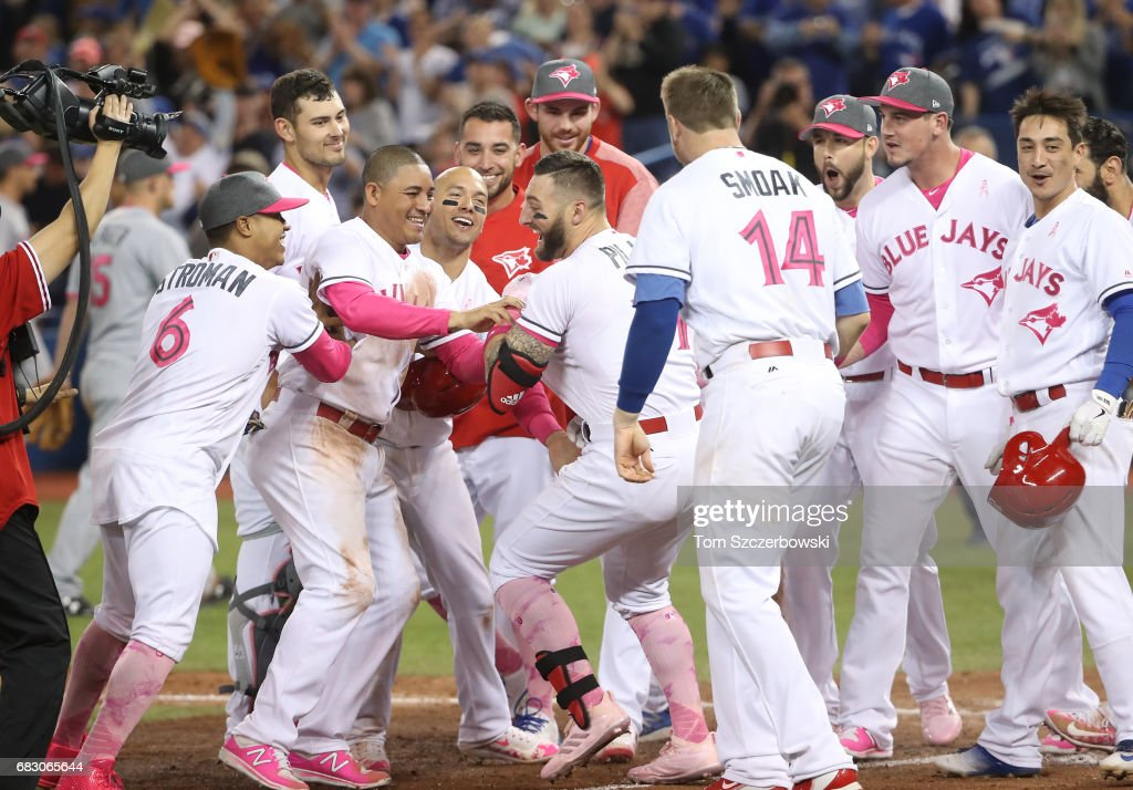 Kevin Pillar #11 of the Toronto Blue Jays is congratulated by teammates after hitting a game-winning solo home run in the ninth inning during MLB game action against the Seattle Mariners at Rogers Centre on May 14, 2017 in Toronto, Canada.