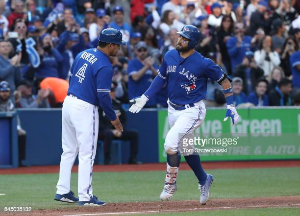 Kevin Pillar of the Toronto Blue Jays is congratulated by third base coach Luis Rivera after hitting a solo home run in the sixth inning during MLB...