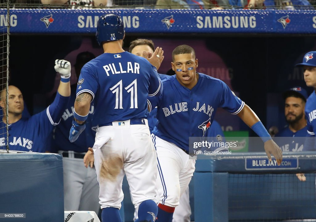 Kevin Pillar #11 of the Toronto Blue Jays is congratulated by Yangervis Solarte #26 and teammates after scoring a run in the sixth inning during MLB game action against the New York Yankees at Rogers Centre on March 31, 2018 in Toronto, Canada.