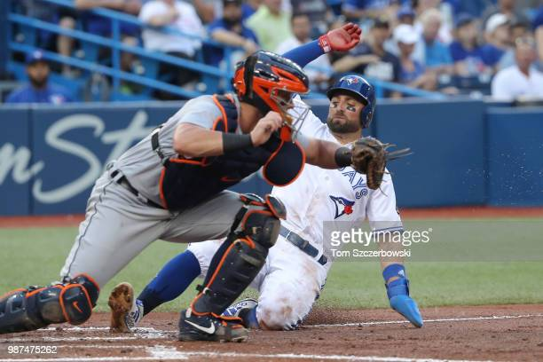 Kevin Pillar of the Toronto Blue Jays is forced out at home plate in the fourth inning during MLB game action as James McCann of the Detroit Tigers...
