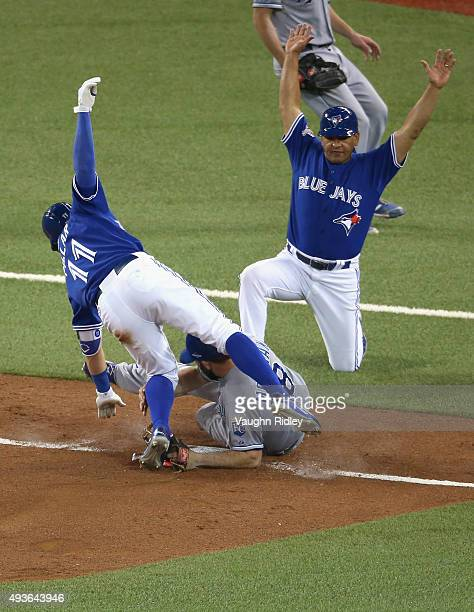 Kevin Pillar of the Toronto Blue Jays is tagged out by Mike Moustakas of the Kansas City Royals in front of third base coach Luis Rivera in the...