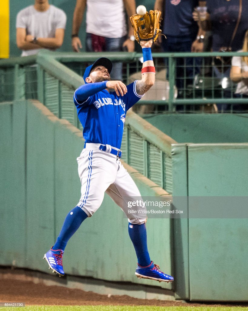 Kevin Pillar #11 of the Toronto Blue Jays leaps as he catches a line drive during the seventh inning of a game against the Boston Red Sox on September 26, 2017 at Fenway Park in Boston, Massachusetts.