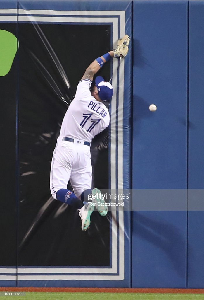 Kevin Pillar #11 of the Toronto Blue Jays slams into the wall but cannot get to a triple hit by Mookie Betts #50 of the Boston Red Sox in the second inning during MLB game action at Rogers Centre on August 9, 2018 in Toronto, Canada.