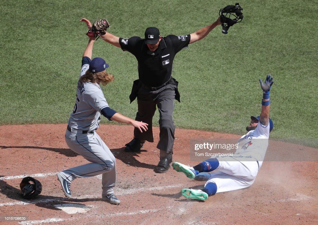 Kevin Pillar #11 of the Toronto Blue Jays slides home safely to score a run in the sixth inning during MLB game action as Ryne Stanek #55 of the Tampa Bay Rays cannot tag him out in time at Rogers Centre on August 12, 2018 in Toronto, Canada.