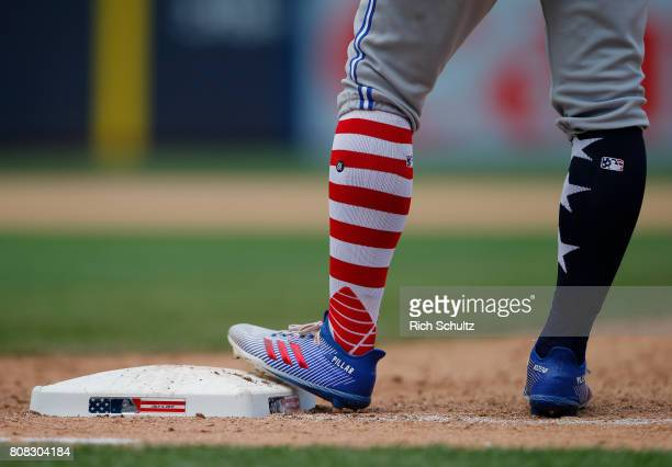 Kevin Pillar of the Toronto Blue Jays stands on first base with special socks and shoes for celebrating Independence Day during a game against the...