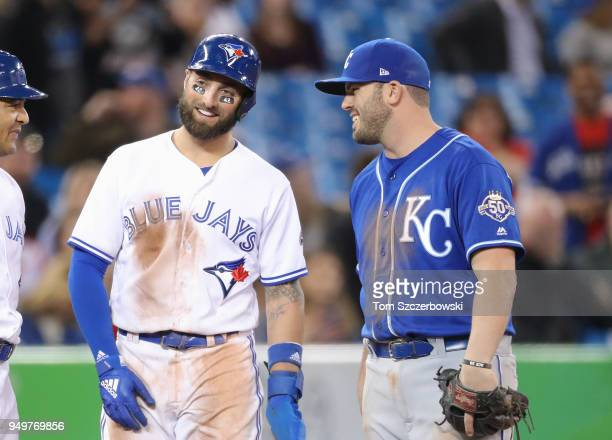 Kevin Pillar of the Toronto Blue Jays waits on third base during a coaching visit to the mound as he talks to Mike Moustakas of the Kansas City...