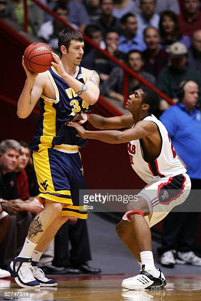 Kevin Pittsnogle of the West Virginia Mountaineers looks to pass around Devonne Giles of the Texas Tech Red Raiders during the Sweet 16 game of the...
