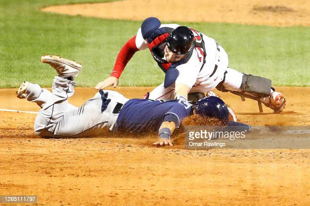 Kevin Plawecki of the Boston Red Sox tags out Michael Perez of the Tampa Bay Rays at home plate at the top of the fourth inning of the game at Fenway...