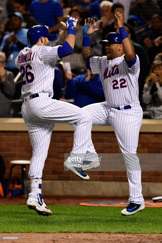 Kevin Plawecki #26 of the New York Mets celebrates his two-run homer with Dominic Smith #22 during the game against the Cincinnati Reds at Citi Field on September 9, 2017 in the Flushing neighborhood of the Queens borough of New York City.
