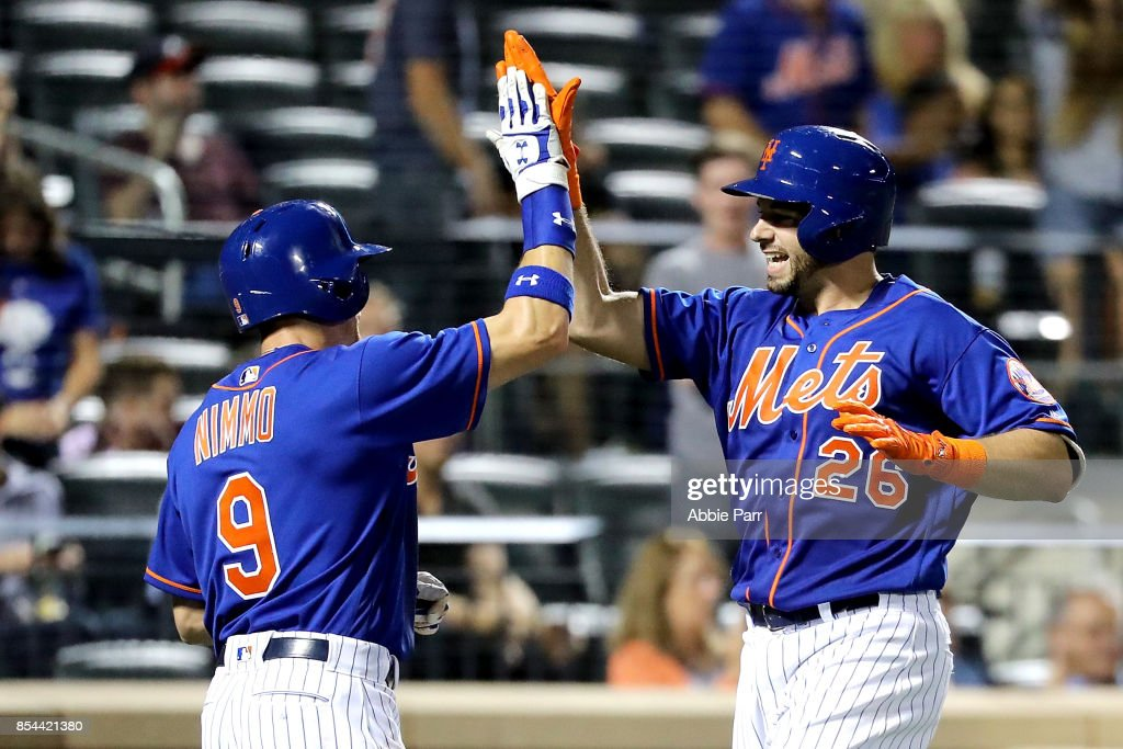 Kevin Plawecki #26 of the New York Mets celebrates with teammate Brandon Nimmo #9 after hitting a two-run home run in the seventh inning against the Atlanta Braves on September 26, 2017 at Citi Field in Flushing neighborhood of the Queens borough of New York City.