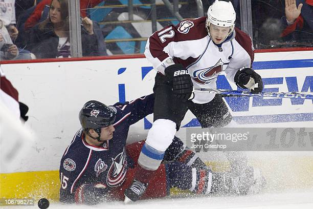 Kevin Porter of the Colorado Avalanche checks Derek Dorsett of the Columbus Blue Jackets to the ice while chasing after a loose puck during the...