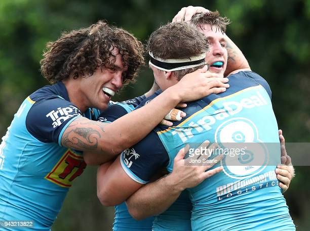 Kevin Proctor Jarrod Wallace and Jai Arrow of the Titans celebrate the winning try during the round five NRL match between the Gold Coast Titans and...