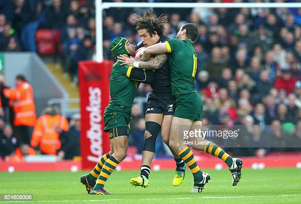Kevin Proctor of New Zealand is tackled by Johnathan Thurston and Boyd Cordner of Australia during the Four Nations Final between New Zealand and...