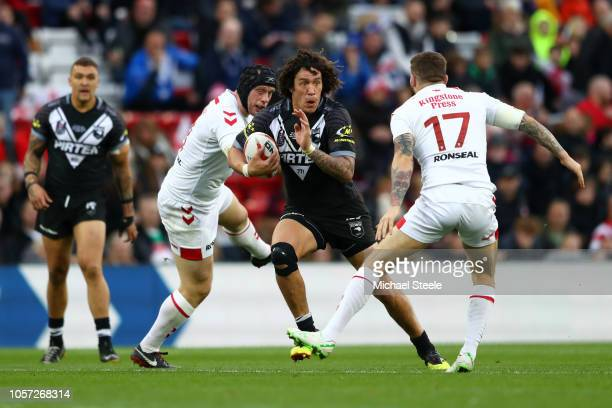 Kevin Proctor of New Zealand runs past Chris Hill and Daryl Clarke of England during the International Series second test match between England and...