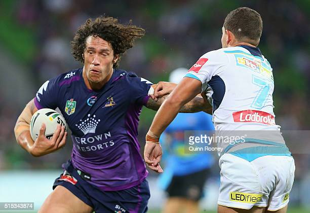Kevin Proctor of the Storm fends off a tackle by Ashley Taylor of the Titans during the round two NRL match between the Melbourne Storm and the Gold...