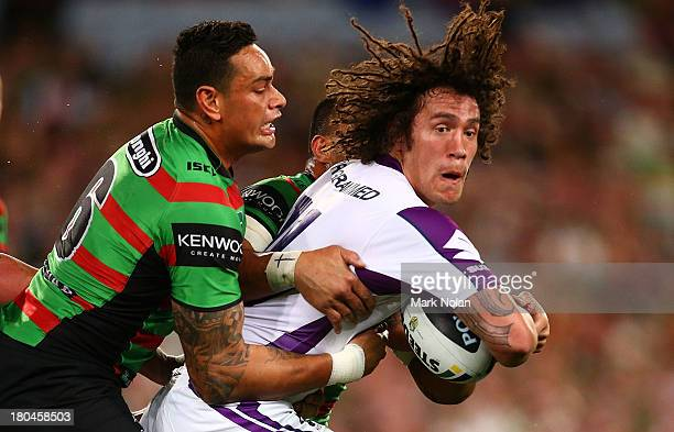 Kevin Proctor of the Storm is tackled by John Sutton of the Rabbitohs during the NRL Qualifying match between the South Sydney Rabbitohs and the...