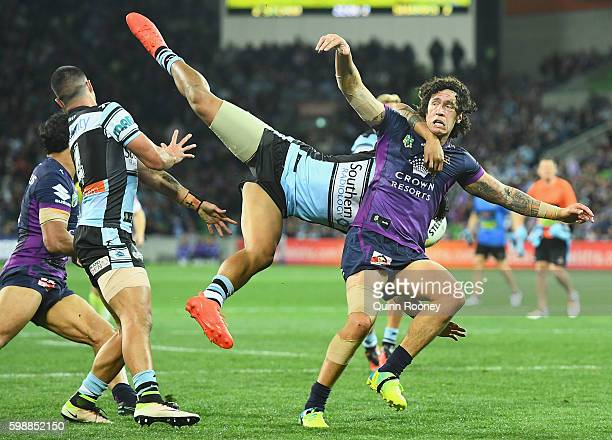 Kevin Proctor of the Storm is tackled by Sosaia Feki of the Sharks during the round 26 NRL match between the Melbourne Storm and the Cronulla Sharks...
