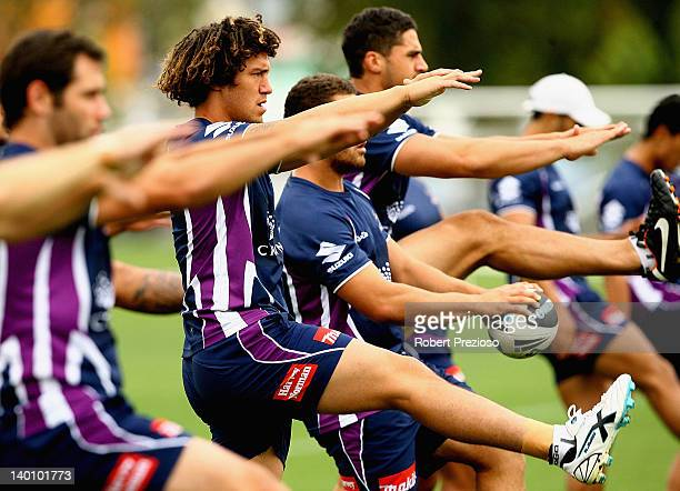 Kevin Proctor of the Storm stretches with teammates during a Melbourne Storm NRL training session at Gosch's Paddock on February 28 2012 in Melbourne...