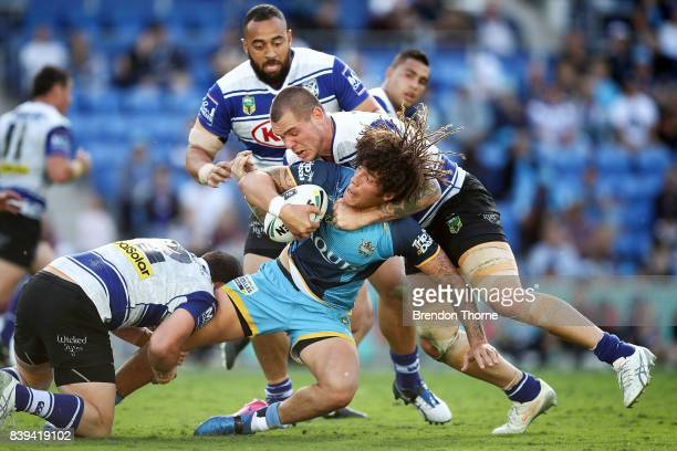 Kevin Proctor of the Titans is tackled by David Klemmer of the Bulldogs during the round 25 NRL match between the Gold Coast Titans and the...