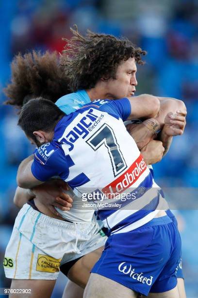 Kevin Proctor of the Titans is tackled by Matt Frawley of the Bulldogs during the round 15 NRL match between the Canterbury Bulldogs and the Gold...