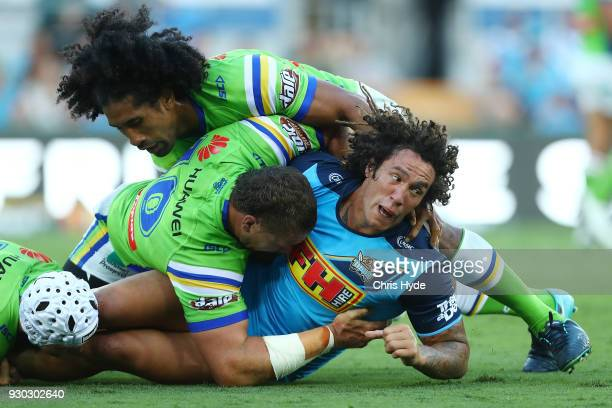 Kevin Proctor of the Titans is tackled during the round one NRL match between the Gold Coast Titans and the Canberra Raiders at Cbus Super Stadium on...