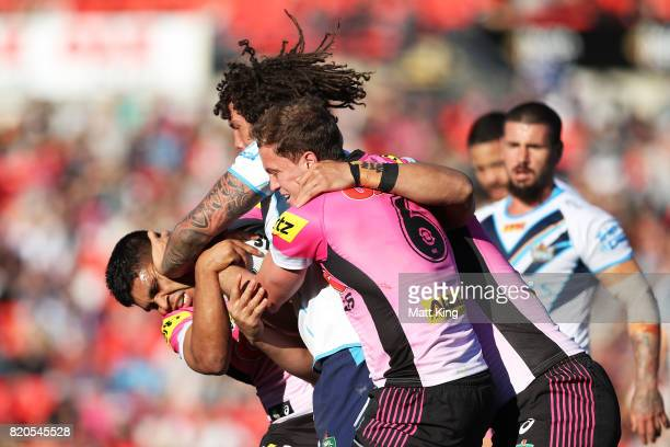 Kevin Proctor of the Titans puts a fend on Tyrone Peachey of the Panthers during the round 20 NRL match between the Penrith Panthers and the Gold...