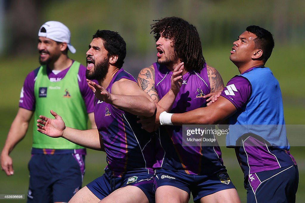 Kevin Proctor (C) Richard Kennar (R) and Jesse Bromwich contest for an AFL football during a Melbourne Storm NRL training session at Gosch's Paddock on August 22, 2014 in Melbourne, Australia.