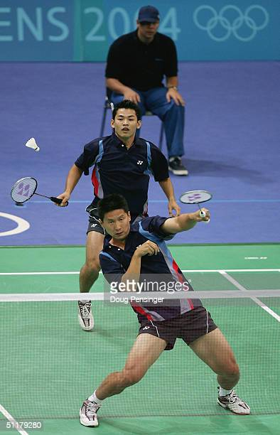 Kevin Qi Han of the USA gets handcuffed trying to return a shot in front of teammate Howard Bach against Jens Eriksen and Marti Lundgaard Hansen of...