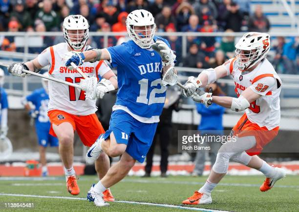 Kevin Quigley of the Duke Blue Devils runs with the ball between the defense of Brett Kennedy and Andrew Helmer of the Syracuse Orange during the...