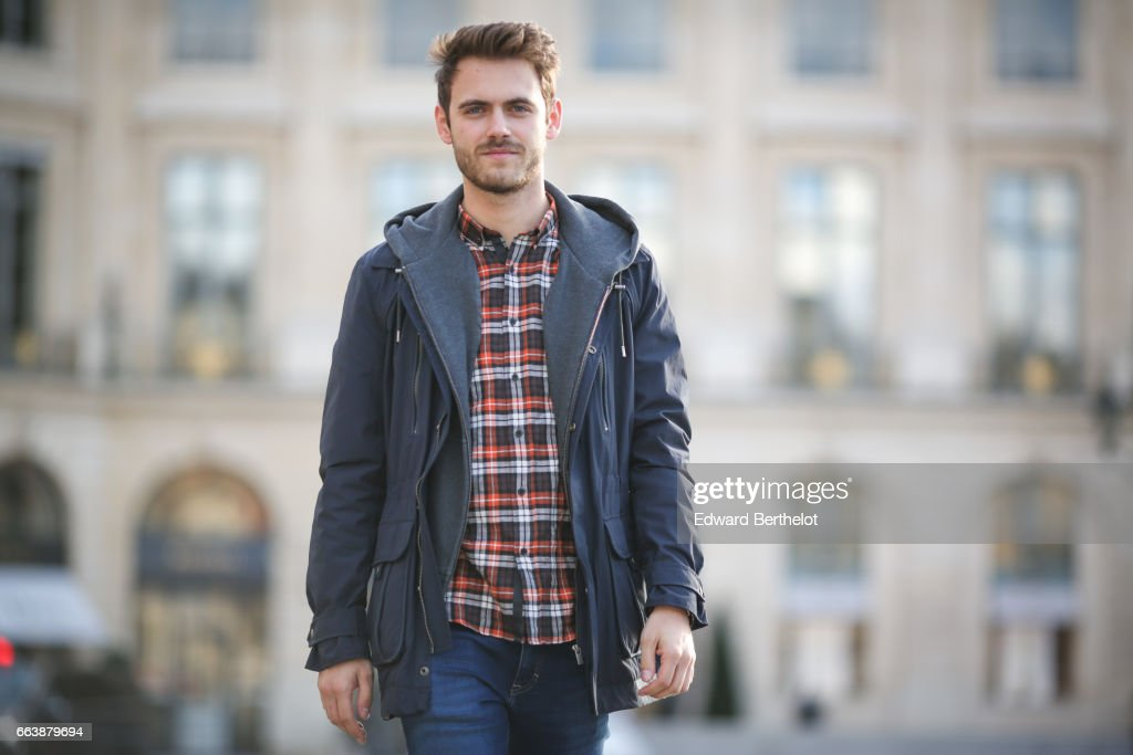 Kevin Ragonneau, fashion and life style blogger, wears a The kooples jacket, The Kooples red tartan shirt, Calvin Klein jeans, Nike Internationalist sneakers shoes, a Daniel Wellington watch, on April 1, 2017 in Paris, France.