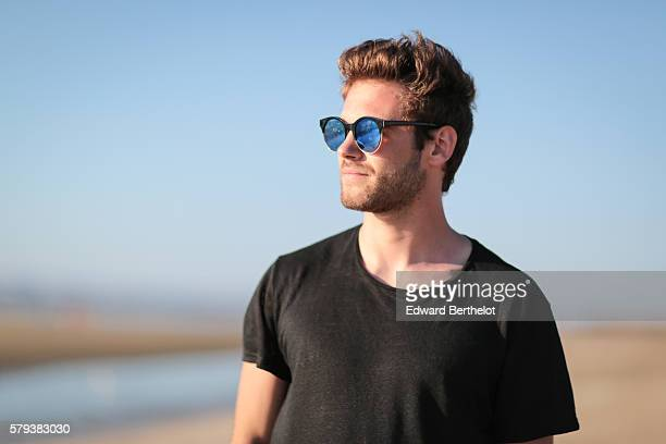 Kevin Ragonneau is wearing a The Kooples black swim short a Zara black tshirt and L'usine a lunettes by Polette sunglasses on the beach on July 23...