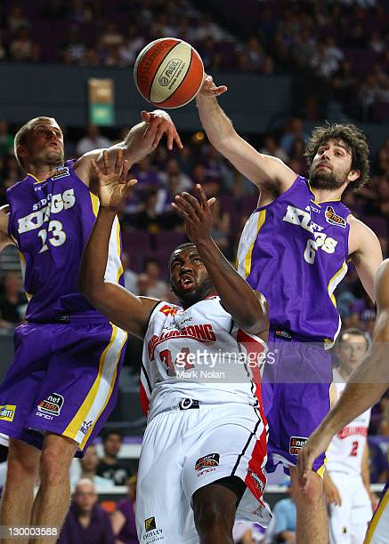 Kevin Ratzsch and Julian Khazzouh of the Kings block Joevan Catron of the Hawksduring the round three NBL match between the Sydney Kings and the...