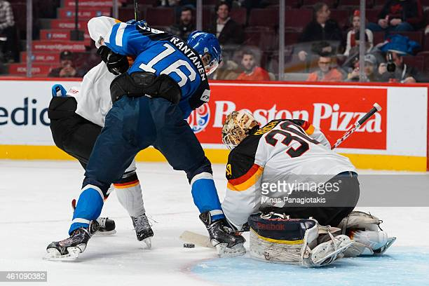 Kevin Reich of Team Germany tries to cover the puck as Mikko Rantanen of Team Finland attempts to get a shot in a preliminary round game during the...