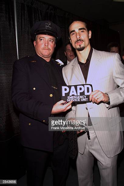 Kevin Richardson of the Backstreet Boys with a Port Authority Police officer backstage at The Concert for New York City at Madison Square Garden in...