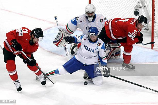 Kevin Romy of Switzerland tries to score against goalkeeper Daniel Bellissimo and Christian Borgatello of Italy during the IIHF World Championship...