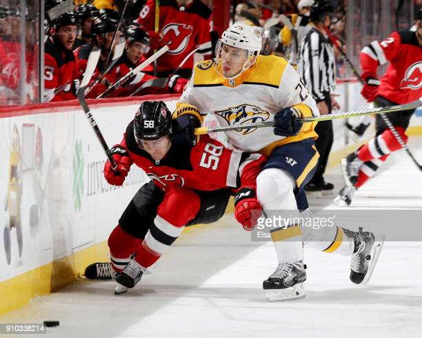 Kevin Rooney of the New Jersey Devils is hit by Alexei Emelin of the Nashville Predators in the second period on January 25 2018 at Prudential Center...