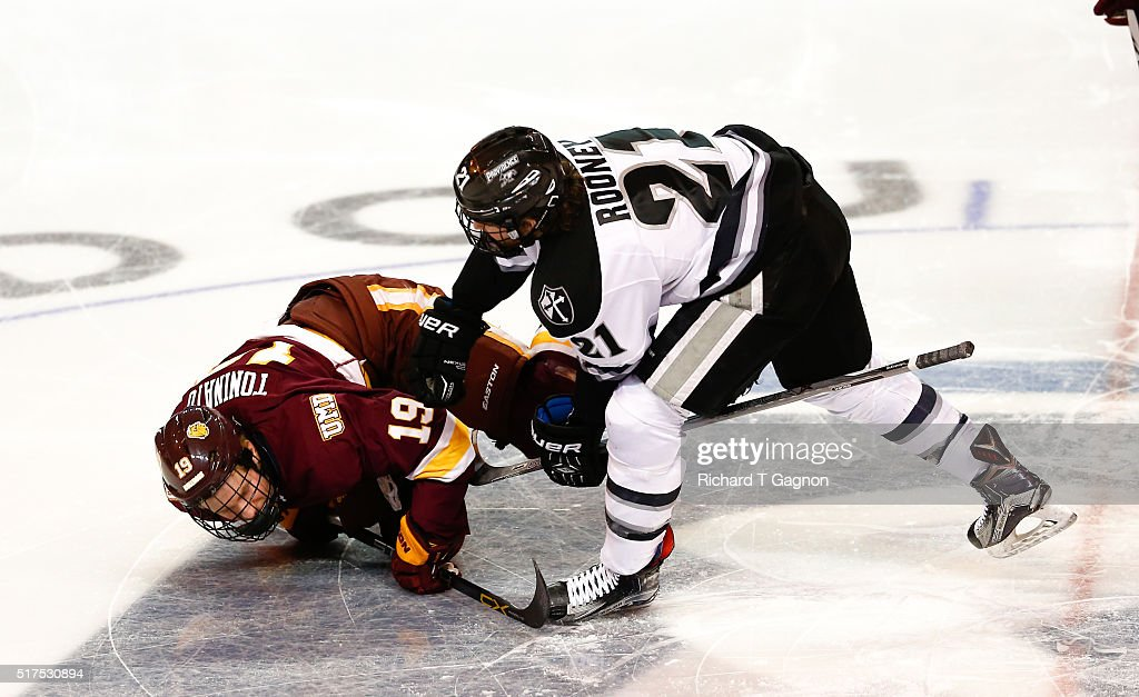 Kevin Rooney #21 of the Providence College Friars checks Dominic Toninato #19 of the Minnesota Duluth Bulldogs to the ice during the opening face-off during game one of the NCAA Division I Men's Ice Hockey Northeast Regional Championship Semifinals at the DCU Center on March 25, 2016 in Worcester, Massachusetts.