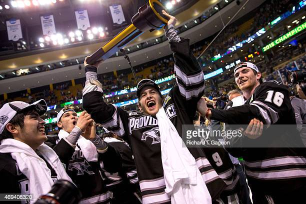 Kevin Rooney of the Providence College Friars lifts the national championship trophy above his head during the 2015 NCAA Division I Men's Hockey...
