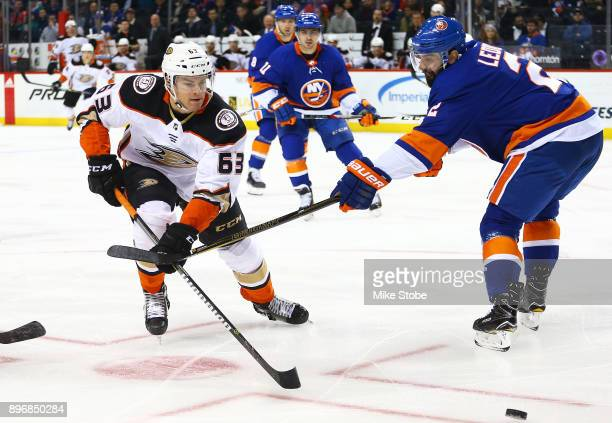 Kevin Roy of the Anaheim Ducks chases down a loose puck amid pressure from Nick Leddy of the New York Islanders during the second period at Barclays...