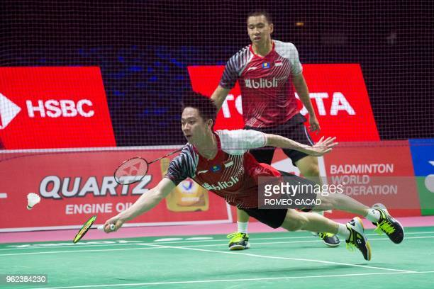 Kevin Sanjaya Sukamuljo of Indonesia dives to hit a return against Liu Cheng and Zhang Nan of China as his teammate Marcus Fernaldi Gideon looks on...